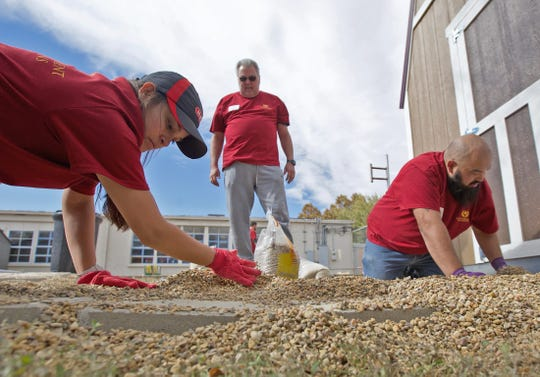 From left: Janet Flores, David Dowd and Rudy Gomez help beautify the exterior of the Boys and Girls Club north side facility Thursday, Nov. 14, 2019.