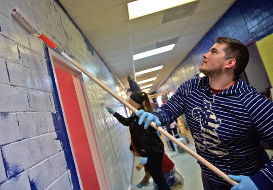 James Baker, right, applies a coat of paint in the hallway at the Boys and Girls Club north side facility Thursday, Nov. 14, 2019.