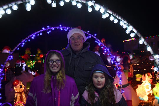 (From left) Hailey, Curtis and Paytlyn Davis pose in front of the front-yard holiday display in Pittsville, Maryland, on Nov. 13, 2019. Curtis, 39, is the girls' uncle, and he looks forward to keeping the tradition alive.