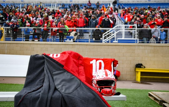 The Britton-Hecla football uniform of Trevor Zuehlke, who is recovering from a serious head injury, is set up on the bench as fans and community members cheer for the team during the Class 9A state football finals on Thursday, Nov. 14, at the Dana J. Dykehouse Stadium in Brookings.