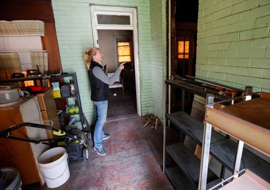 Amy Blansit looks through one of the homes she is rehabilitating for low-income residents.