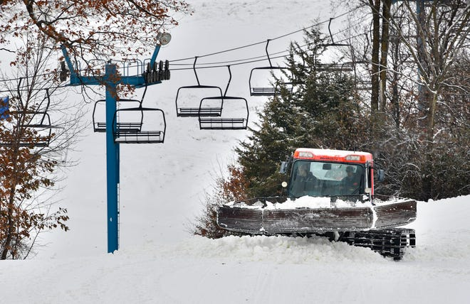 Crews groom newly-made snow on one of the routes at Powder Ridge Thursday, Nov. 14, 2019, near Kimball. Recent cold temperatures have allowed enough snow to be made to open this weekend.