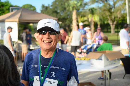 "2019 ""Run for the Village"" 5K & Fun Run participant Domingo Ngo, of Palm City, enjoys the after-race festivities on the grounds of the Village Club & Preserve in Palm City."