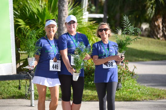 "Pam Gobel, left, Carolyn Turner and Linda Sagarino show off their custom medals and palm trees, which were awarded to those who placed in each age category of the ""Run for the Village"" 5K & Fun Run in Palm City on Oct. 5, 2019."