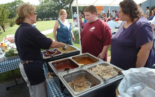 In this 2010 photo, Where Pigs Fly restaurant owner Kelly Devine serves an 8th grade student at an annual barbeque luncheon at Positive Outcomes Charter School in Camden.    .