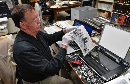 John Yates prepares to digitally scan an historic photo of downtown Wichita Falls from the Wichita County Archives. Photographs and documents from the archive files will be availabe online.