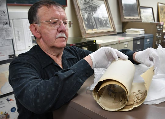 John Yates carefully inspects a historic panoramic photograph from the Wichita County Archives. Yates is helping digitize the collection, some of which  are deteriorating badly.