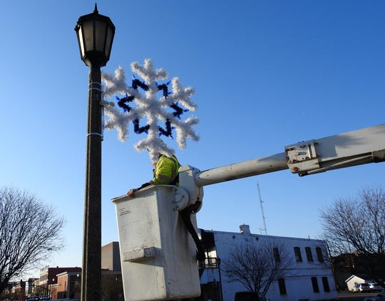 Workers with the City of Coshocton assisted Our Town Coshocton with hanging snowflake Christmas decorations Thursday on lampposts along Main Street. Decorations were hung in preparation of the annual Miracle on Main Street next Friday.