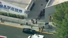 People are lead out of Saugus High School after reports of a shooting on Nov. 14, 2019 in Santa Clarita, Calif. The Los Angeles County Sheriff's Department says on Twitter that deputies are responding to the high school about 30 miles northwest of downtown Los Angeles. The sheriff's office says a male suspect in black clothing was seen at the school.