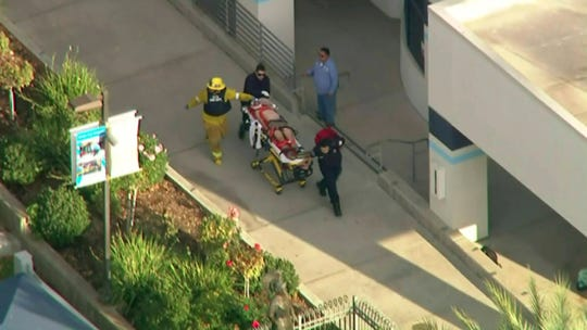 In this photo from video provided by KTLA-TV paramedics transport an injured person after a shooting at Saugus High School in Santa Clarita, Calif., on Nov. 14, 2019.