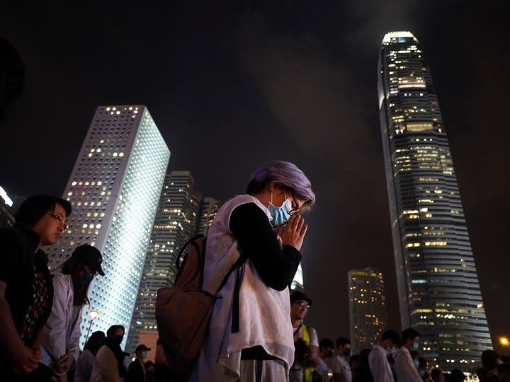 A man offers prayer as firemen and medical volunteers attend a rally in Hong Kong on Nov. 14, 2019.