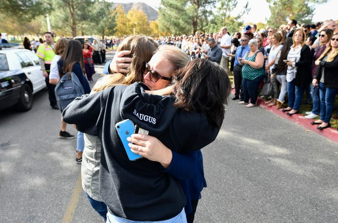 A parent is reunited with her children after a student was killed and other injured during a shooting at Saugus High School in Santa Clarita, Calif. on Nov. 14, 2019.