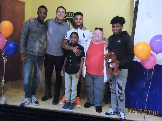 Janet Hans (center, red shirt) with sons Nagid, Joe, Justin, Naeim and Hasahn.