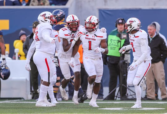 Nov 9, 2019; Morgantown, WV, USA; Texas Tech Red Raiders linebacker Jordyn Brooks (1) celebrates with linebacker Xavier Benson (37) and defensive back Adrian Frye (7) after recovering a fumble against the West Virginia Mountaineers during the third quarter at Mountaineer Field at Milan Puskar Stadium. Mandatory Credit: Ben Queen-USA TODAY Sports