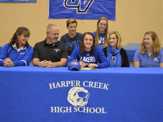 Harper Creek swimmer Alysa Wager announces she will attend Grand Valley State University at a signing ceremony at the Harper Creek High School pool. She is joined by her coaches and family.
