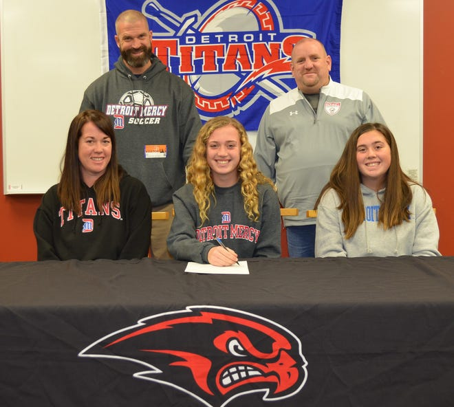 Olivia Zulewski commits to the University of Detroit Mercy at a National Letter of Intent signing ceremony at Marshall High School on Thursday. She is joined by her family and coach.