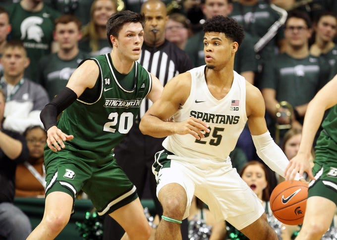 Nov 10, 2019; East Lansing, MI, USA; Michigan State Spartans forward Malik Hall (25) is defended by Binghamton Bearcats forward George Tinsley (20) during the first half of a game at Breslin Center. Mandatory Credit: Mike Carter-USA TODAY Sports