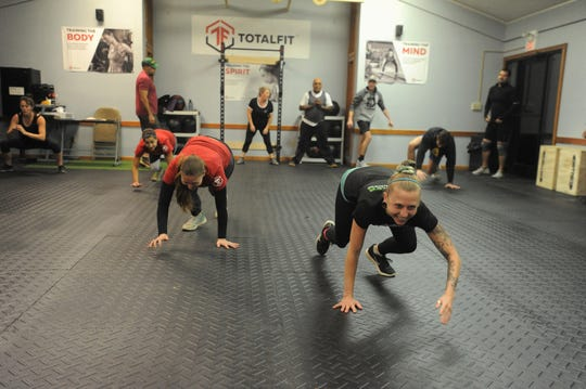 Teresa Bowser, right, and Mandy Holbert do bear crawls in TotalFit at The Ridge, where the new fitness program focuses on training participants' minds, bodies and spirits.