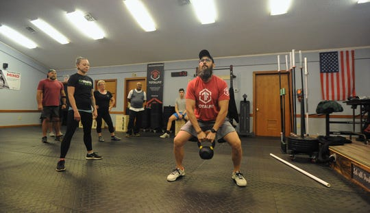 Trent Holbert demonstrates the proper technique for a sumo dead lift using a kettlebell.
