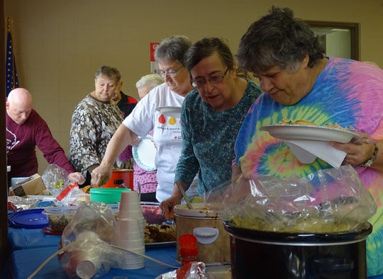 """Mary D. Smith, right, and others fill their plates during the """"Give Thanks Together"""" potluck at the Bucyrus Area YMCA on Thursday."""