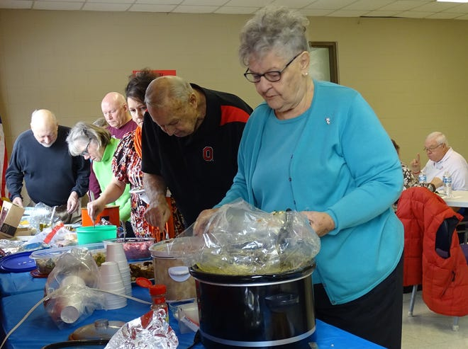 """Donna Bauer, right, and others fill their plates during the """"Give Thanks Together"""" potluck at the Bucyrus Area YMCA on Thursday."""