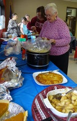 """Karen Harman, right, and others fill their plates during the """"Give Thanks Together"""" potluck at the Bucyrus Area YMCA on Thursday."""