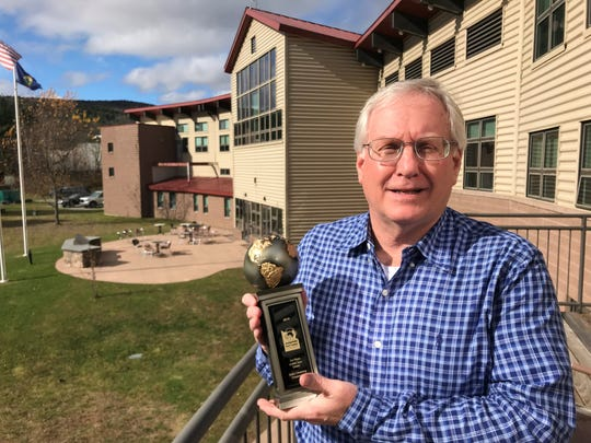 Agri-Mark CEO Ed Townley, on a balcony outside the co-op's offices in Waitsfield, holds one of the many awards Cabot has received for its cheese.