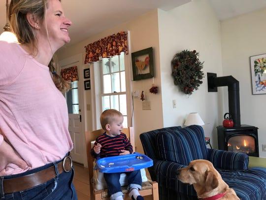 Merritt entertains himself feeding the family dog while his mother, Alison Kosakowski, looks on.