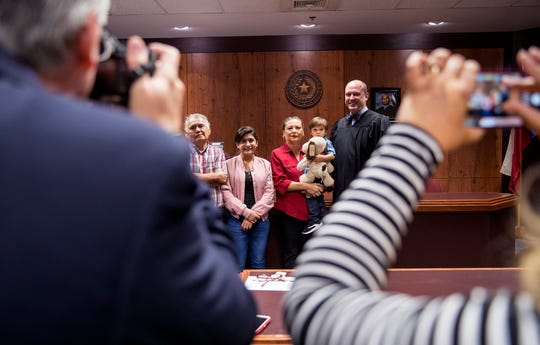 County Court-at-Law Judge Timothy McCoy, right, takes photos with a family following an approval of an adoption on Friday, November 15, 2019 in Corpus Christi. The number of children being adopted from the state's foster care has reached a four-year high, according to newly released data.