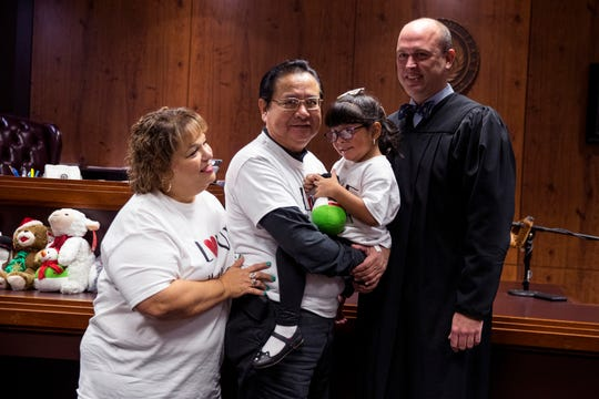 Josefa Barrera, from left, Rafael Barrera, and Reina Barrera, 4, take a photo with County Court at Law #5 Judge Timothy McCoy on Friday, November 15, 2019 following the finalization of Reina's adoption.
