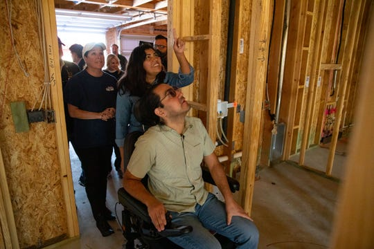 Wounded veteran Julio Martinez and his wife Manquetzalli walk in to the home being given to them by Operation FINALLY HOME to read notes of love written on the studs for them on on Friday, Nov. 15, 2019.