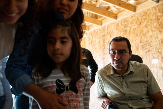 Wounded veteran Julio Martinez with his family in the home being given to them by Operation FINALLY HOME to reads notes of love written on the studs of the home for him and his family on Friday, Nov. 15, 2019.