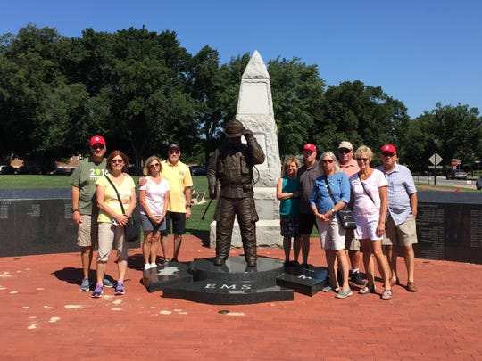 Members of the College Hill Beer Club visit a firefighter memorial in Delaware. Debbie and Don Wolterman are the second couple to the right of the statue.