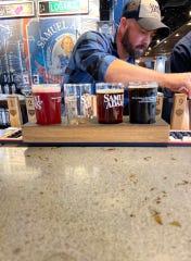 Cincinnati Samuel Adams taproom's Head Brewer Chris Siegman pours beer for a flight.