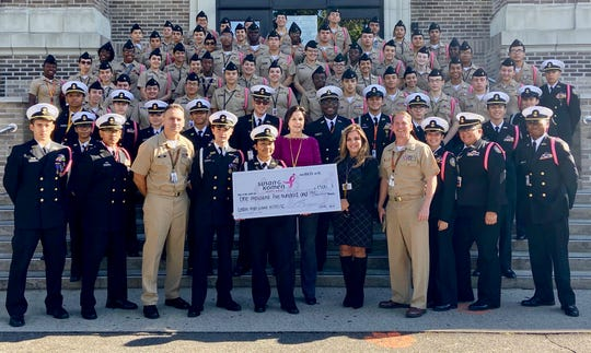 Linden High School Navy Junior ROTC cadets present a check for $1,500 to Tina Jacobs, the director of community health for Susan G. Komen New Jersey. At center of front row are instructor Chief Petty Officer Mark Velez; Regimental Commanding Officer Mario Rodriguez; Regimental Executive Officer Licxi Cardoso; Tina Jacobs; LHS Principal Yelena Horré; and Commander Boyd Decker, senior Naval Science instructor.