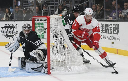 Detroit Red Wings center Dylan Larkin (71) brings the puck around the net as Los Angeles Kings defenseman Ben Hutton (15) pursues as goalie Jonathan Quick defends the net during the first period of an NHL hockey game Thursday, Nov. 14, 2019, in Los Angeles.