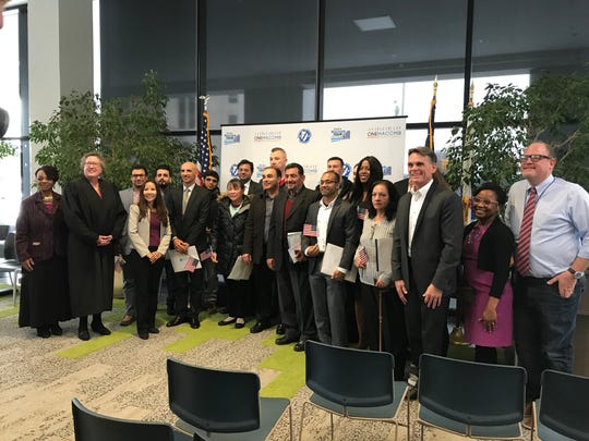 Seventeen people representing 11 countries take a photograph with officials after becoming U.S. citizens during a naturalization ceremony Nov. 15, 2019 in Mount Clemens.