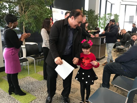 Majid Dieaakbary, 56, of Canton holds hands with his daughter, Nafas, 5, after receiving a certificate showing he is a U.S. citizen during a naturalization ceremony Nov. 15, 2019 in Mount Clemens.