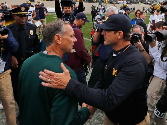 Mark Dantonio and Jim Harbaugh shake hands at the end of the 2016 game, won by Michigan 32–23.