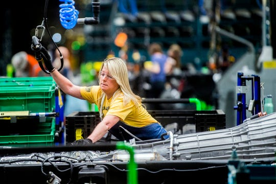 General Motors employees work on the chassis line as they build the frame, power train and suspension onto the truck's body at the Flint Assembly Plant in Flint, Mich.