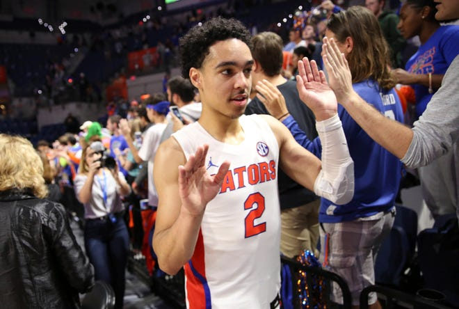 Florida guard Andrew Nembhard (2) celebrates with fans after the victory over Towson.