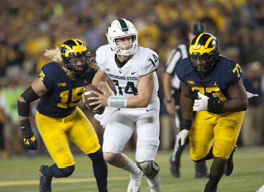 Michigan State quarterback Brian Lewerke escapes the Michigan defense during the Spartans' win in Ann Arbor in 2017.
