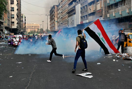 Riot police fire tear gas during clashes between Iraqi security forces and anti-Government protesters in Baghdad, Iraq, Thursday, Nov. 14, 2019.