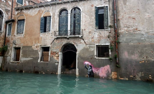 Banksy's migrant child mural is partially submerged in Venice, Italy on Friday.