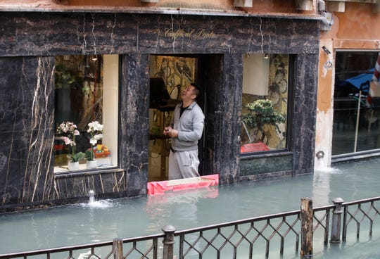 A man looks up from inside a cafe in Venice on Friday.