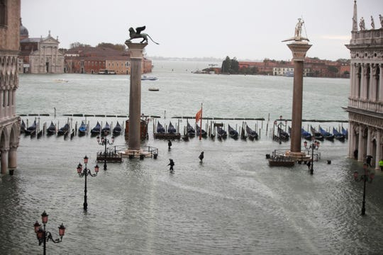 People make their way in a flooded St. Mark's Square in Venice on Friday.