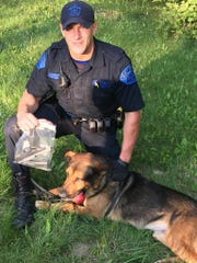 Michigan State Trooper Matt Unterbrink poses with his partner Boz, a firearm tracking dog