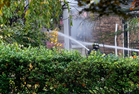 In this Oct. 29, 2019 file photo, Woodbridge firefighters work to extinguish the scene of a plane crash at a home in Woodbridge, N.J.