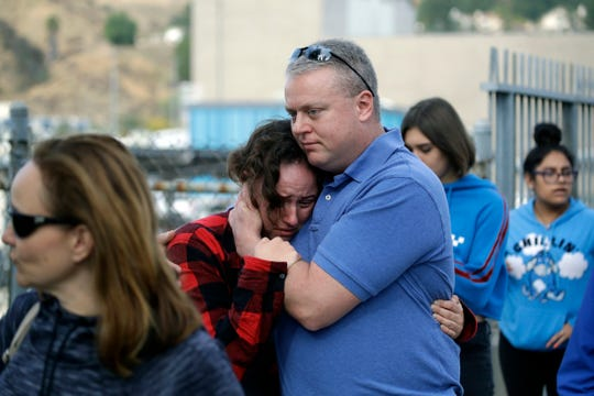 Students are escorted out of Saugus High School as some parents join them after reports of a shooting on Thursday, Nov. 14, 2019, in Santa Clarita, Calif.