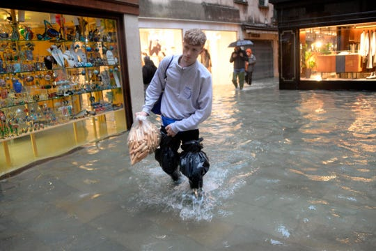 A man holding a bag of what appear to be breadsticks wades through water, in Venice on Friday.